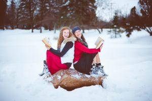 雪の上に座る2人の女性