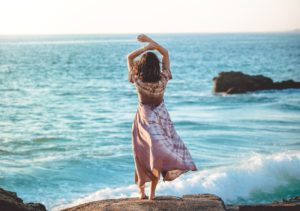 海の前に立つ後ろ姿の女性