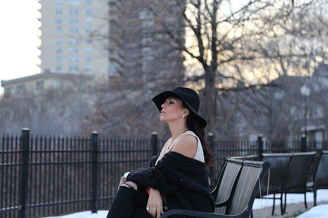 ベンチに座る黒い帽子の女性